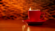 Cup of coffee is on the table on a red saucer video