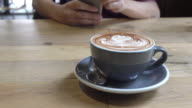 cup of coffee on wood table with man using smart phone background in coffee shop. video