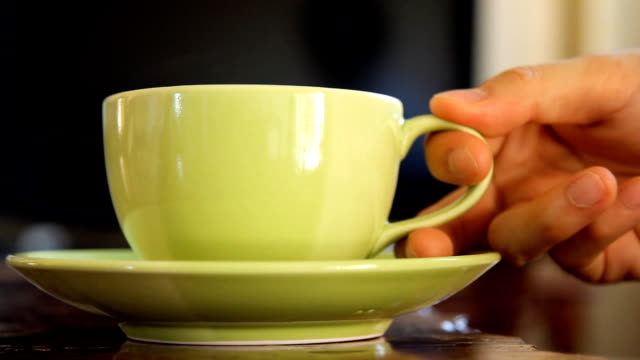 cup of coffee, tea, or hot drink beverage with steam, with hand picking up and put down video