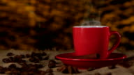 Cup of coffee with cinnamon and beans scattered on the table. Blurred background video