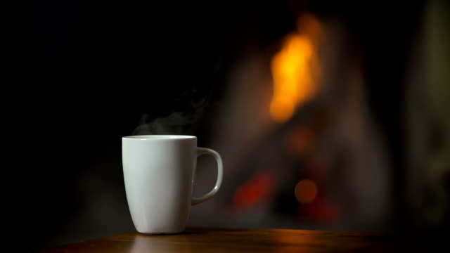 Cup of hot beverage in front of a burning fireplace video