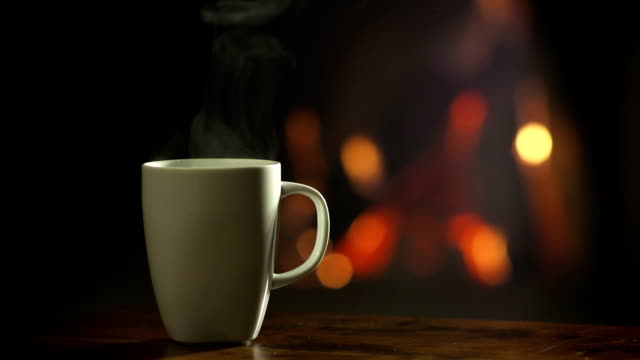 Cup of hot beverage in front of a fireplace video