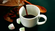 cup of hot chocolate, cinnamon sticks, marshmallows and chocolate bar on black background video