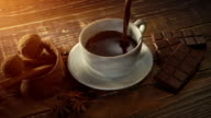 cup of hot chocolate, cinnamon sticks, nuts and chocolate bar on wooden table video