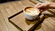 A Cup of hot latte art coffee on wooden table video