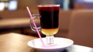 A cup of hot mulled wine on a table with pink straw video