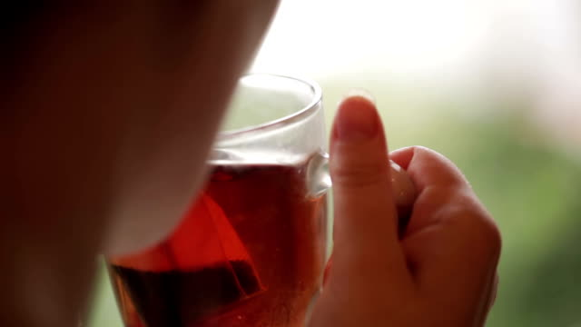 Cup of tea in hands and cold rain. video