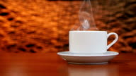 Cup on a white saucer of hot coffee on the aroma spreads room video
