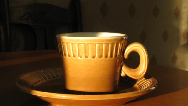Cup with hot coffee on saucer. Time lapse. Moving shadow. video
