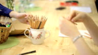 Cup with set of pencil on table, women take it, start to work. On table is empty sheet of paper video