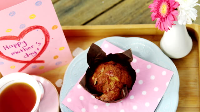 Cupcake, tea, flower vase and happy mothers day greetings card in tray video
