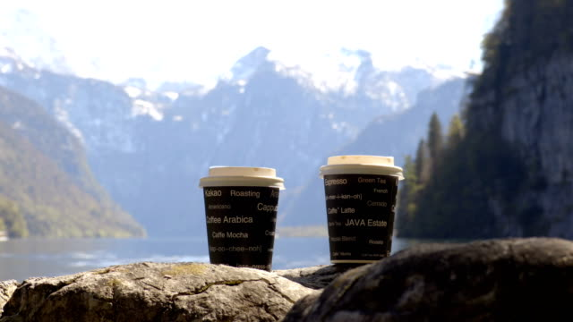 Cups of coffee in the morning next to the lake in mountains. video