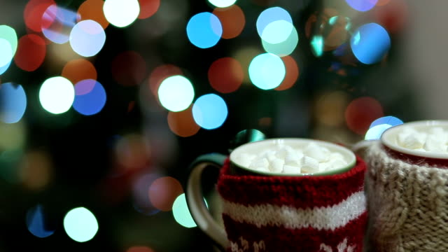 Cups of hot cocoa with marshmallow with Christmas decorations at home, Christmas tree on background, cozy mood video