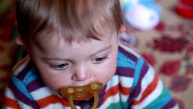 Curious baby with pacifier looking at camera video