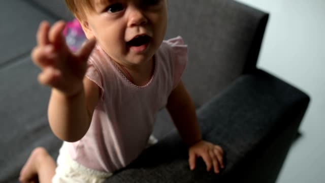Curious cute toddler sitting on the sofa video