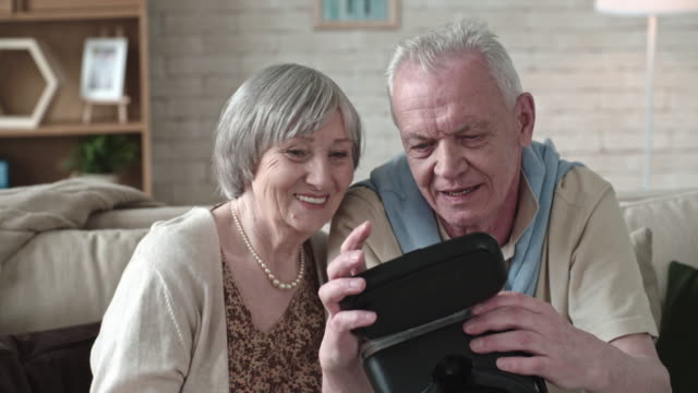 Curious Elderly Couple Looking at VR Goggles video