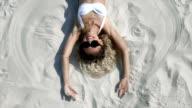 Curled girl in white bikini sunbathing on beach sand video
