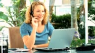 Curly blond haired woman taking a phone call video