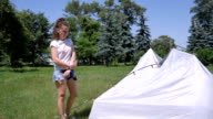 Curly girl have a good time near the tent in park video