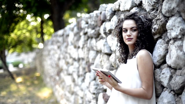 Curly hair female with touchpad learning in the city video