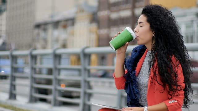 Curly pretty lady drinks coffee outside video