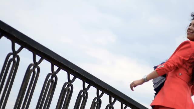 Curly stylish brunette at the bridge video