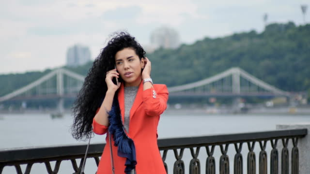 Curly woman talks on her phone at the bridge video