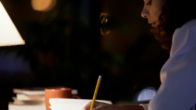 Curly-haired girl sitting in cafe, writing a diary about her dreams and memories video