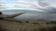 Curonian lagoon shore with people on cement pier, time lapse video