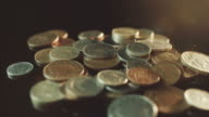 UK Currency pounds coins rotating amongst other UK currency coins in 4K. video