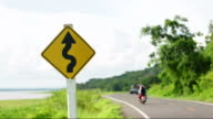 Curve warning sign with motocycle and car moving video