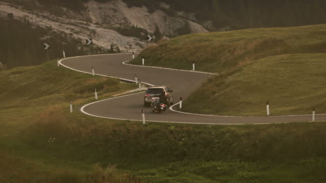 Custom motorbike overtaking a car on mountain road video