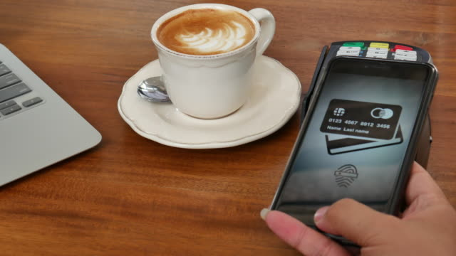 Customer buying his take-away coffee with smartphone video