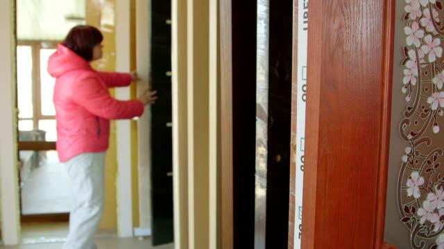 Customer chooses inner wooden door in doors store showroom video