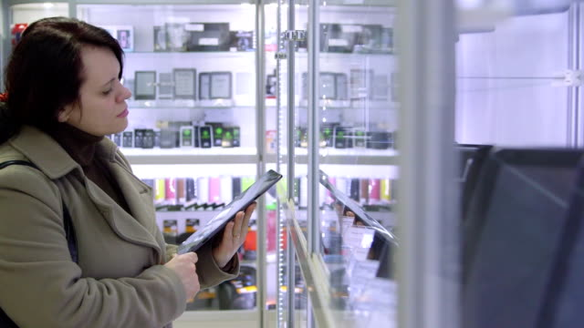 DOLLY: Customer looking for digital tablet in electronics store video