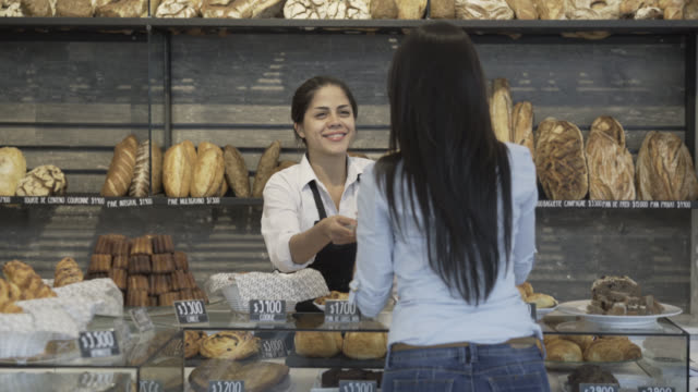 Customer ordering in the bakery counter and saleswoman helping her video