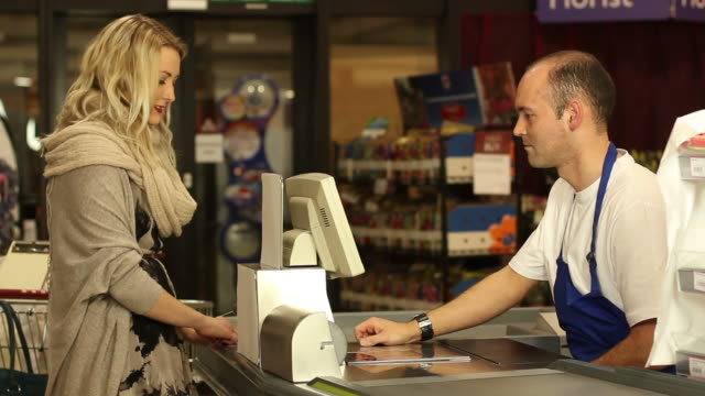 Customer paying for shopping at supermarket video
