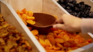 Customer purchases dried apricots in grocery video