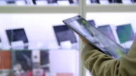 DOLLY: Customer testing new digital tablet at electronics store video