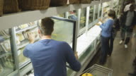 Customers shopping in the frozen section of a supermarket video