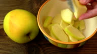 Cut into slices of apples in a bowl for jam on the wooden table video