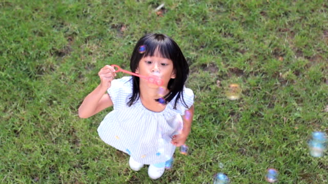 Cute Asian Girl Looks Up While Making Bubbles video
