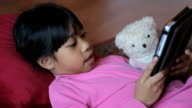 Cute Asian Girl Reads Story To Teddy Bear video