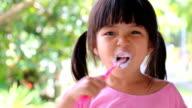 Cute Asian Little Girl Brushing Teeth video