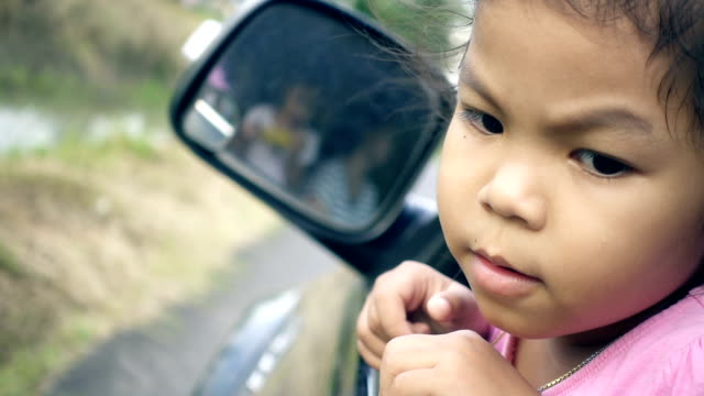 Cute asian little girl is looking around in outside while car moving video