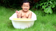 Cute baby boy bathing outdoors in a tub video