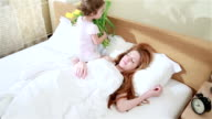Cute baby brings flowers to her mother in bed in the morning. video