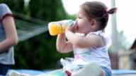 cute baby girl drinking orange juice from the bottle video
