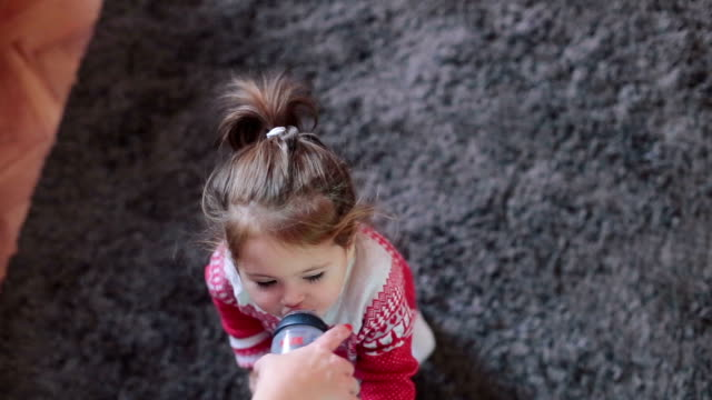 cute baby girl in christmas clothing drinking water from bottle video