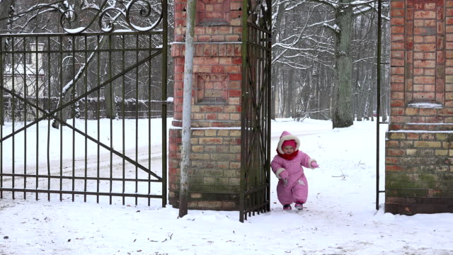 cute baby girl in overall walk through snowy retro park gate in winter. FullHD video